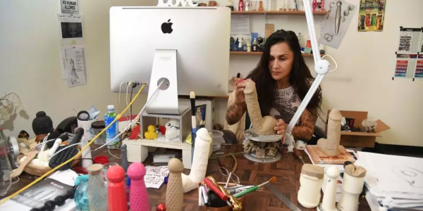 A woman sculpting a dildo at her desk